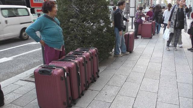 도쿄 긴자 거리의 중국인 관광객들, 이른바 '폭탄쇼핑'을 위해 단체로 가방을 맞춘 듯
