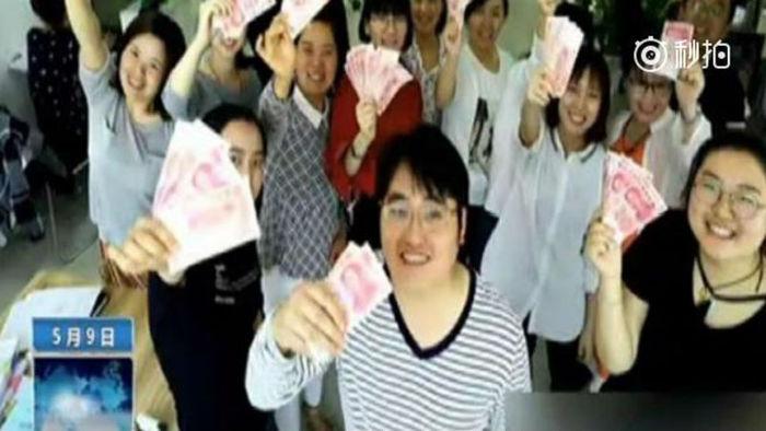 직원들이 상금을 들고 웃고 있는 사진