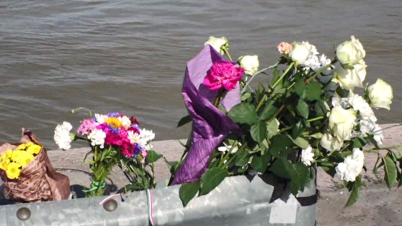 Flowers and candles' beside the Danube     Continuing